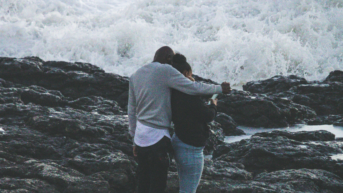 [Image description: Couple stands in front of crashing waves.] via Unsplash