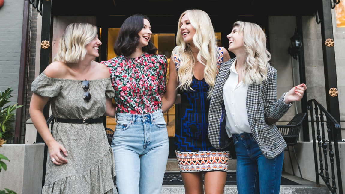 [Image Description: four women standing and chatting outside a building]. Via Unsplash