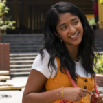 "[Image Description: A still from ""Never Have I Ever"": a South Asian teenage girl with black hair is smiling, facing away from the camera] Via Netflix Media Center"