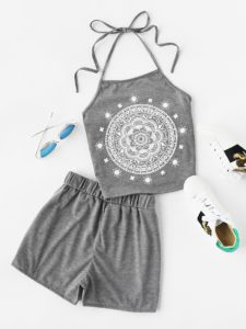 A halter-neck top with graphic print and matching shorts, sunglasses, and shoes.