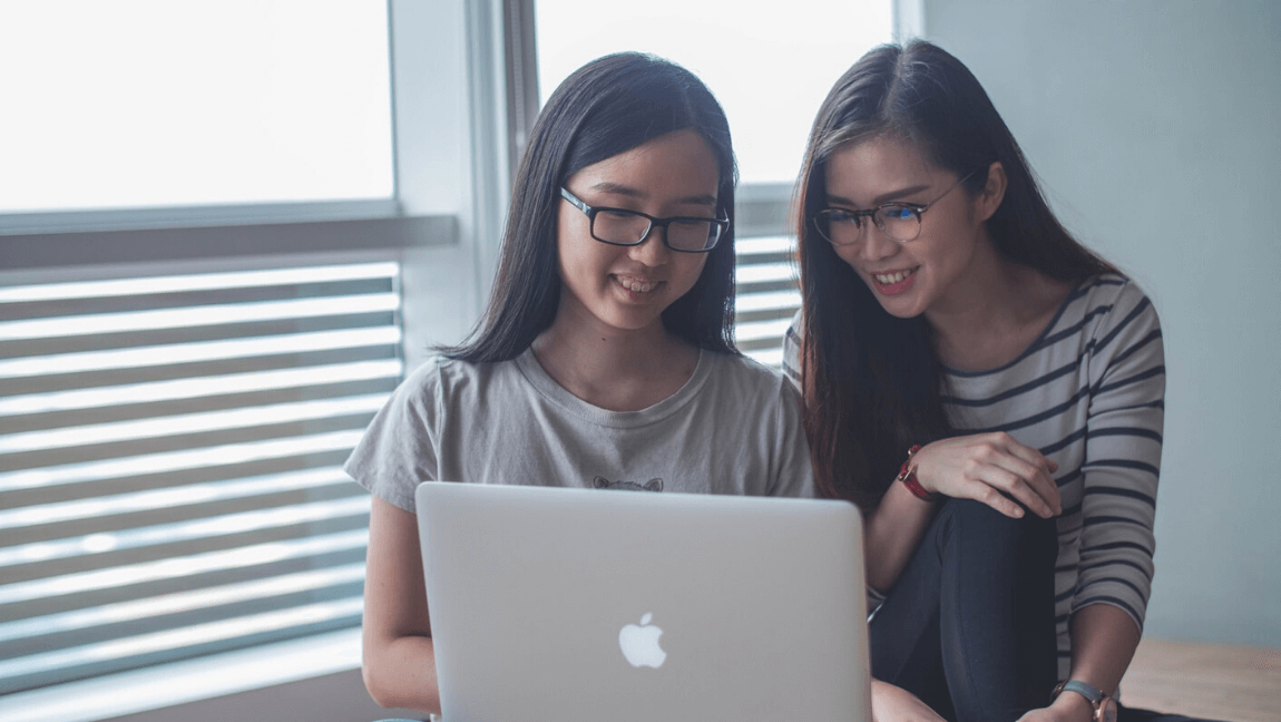 Two women working together on a coding project.