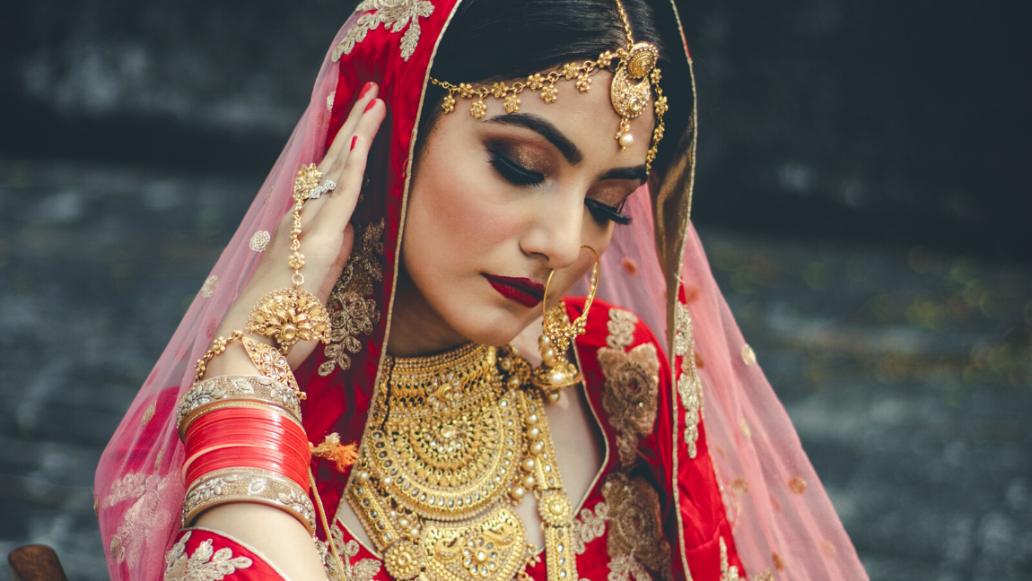 An Indian woman dressed in a red sari and wearing gold jewellery.