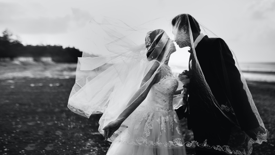 A grayscale shot of a bride and groom kissing.