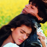 [Image description: Standing in a field of yellow flowers, a woman with brown skin and brown hair wearing a white shirt hugs a man with brown skin and brown hair wearing a leather jacket and a camouflaged backpack.] Via Yash Raj Films