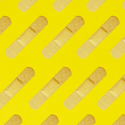 [Image description: Bandaids laid across a yellow wall.] via Unsplash