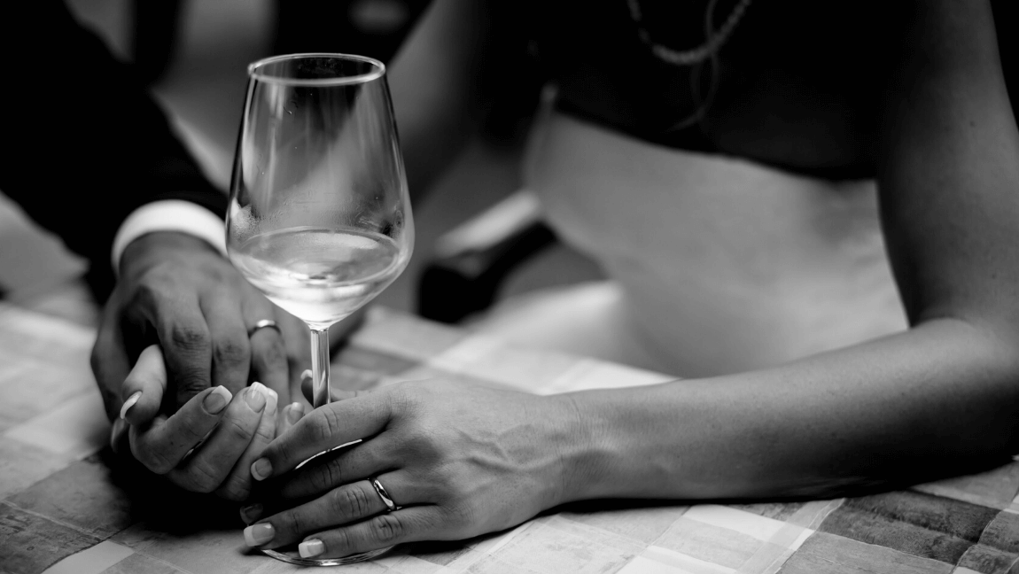 Grayscale photo of a man holding hand of woman holding a wine glass