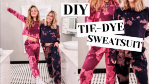 Two blond girls wear DIY tie dye sweatsuits. One girl wears a pink one and the other wears a black one in a checkerboard bathroom.