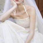 A bride wearing a wedding dress and veil sitting on some steps with a disappointed expression.