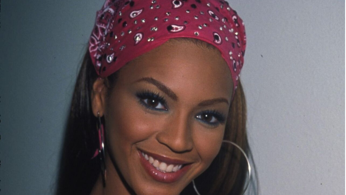Beyonce wearing a pink bandana and silver hoop earrings.