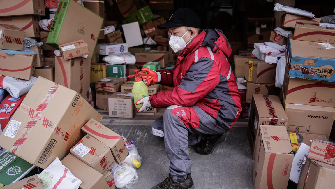 A delivery worker wears a face mask and red jacket and holds a spray bottle with a pile of packages around him.