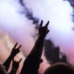 [Image description: concert-goers hold up their hands in the rock sign] via Unsplash