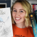 Blond girl wearing an orange Camp Half Blood shirt and holding Percy Jackson books and coloring book.