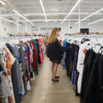 Girl looking through racks of clothes at a thrift store