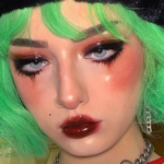 E-girl with green hair wearing grungy makeup and a black beanie with silver chain jewelry.