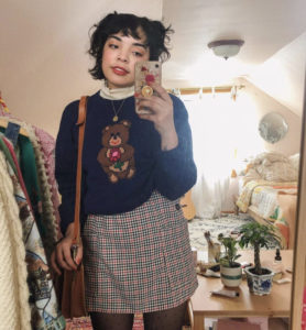YouTuber Diana Chamomile wearing a sweater and a plaid skirt