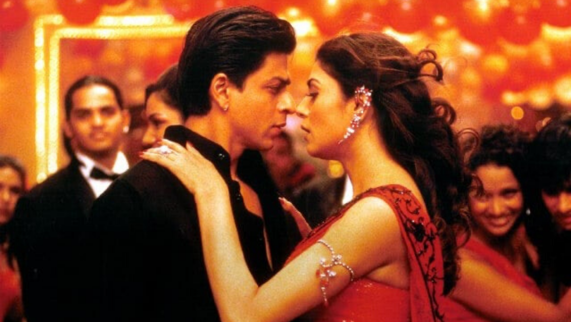Attribution: [Image description: Still from (Main Hoon Na):A woman in a red saree and a man wearing black are locked in an embrace while a crowd looks on.] Via movies.ndtv.com