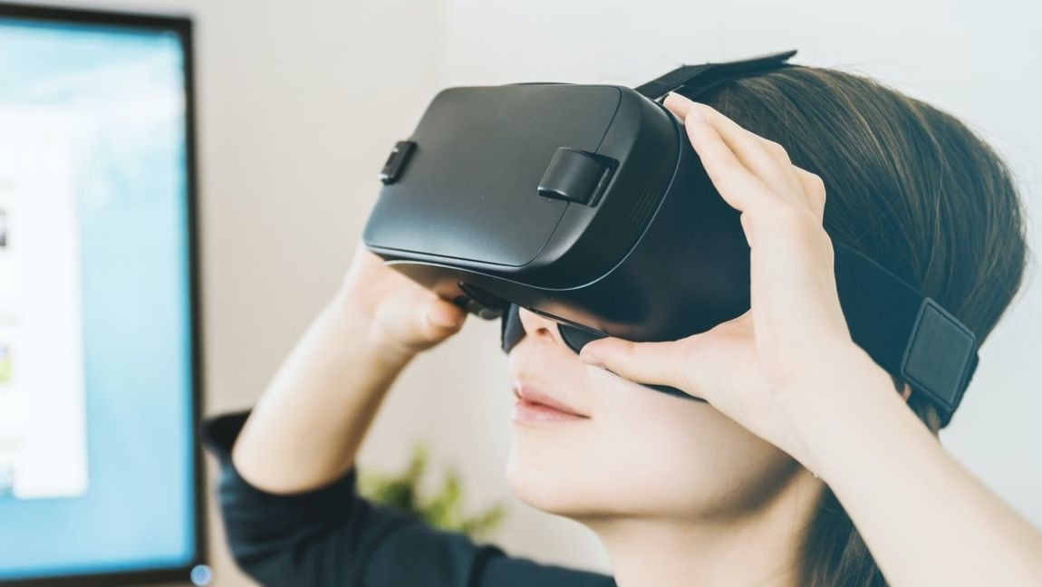 A woman looking up wearing a VR headset.
