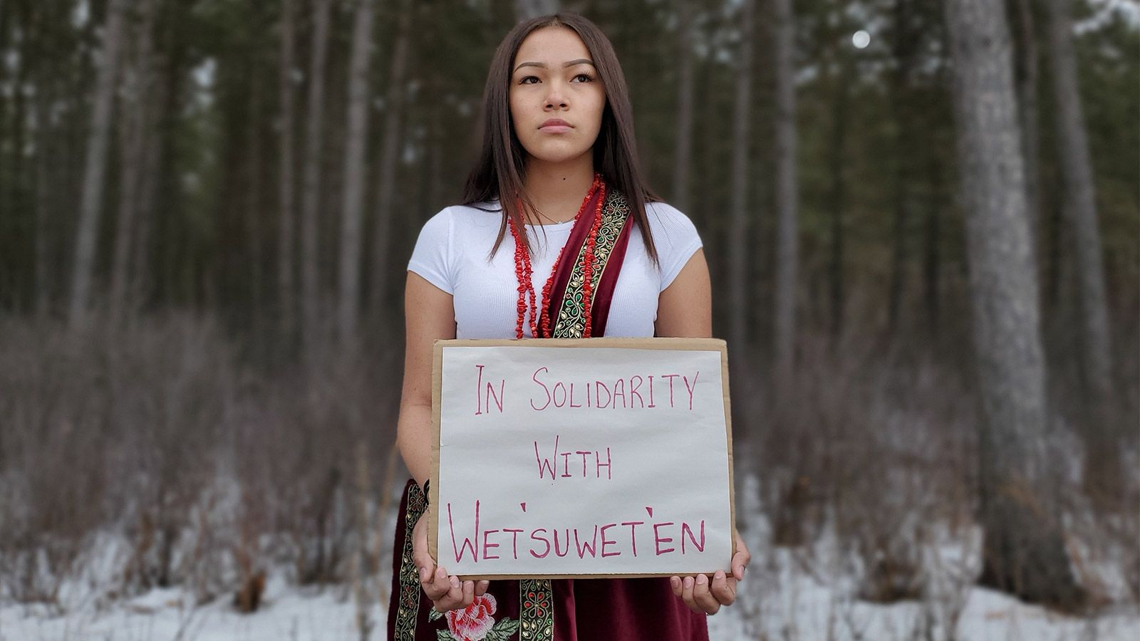Autumn Peltier, a youth climate activist, standing holding a sign that says 'In Solidarity with Wetsuweten'