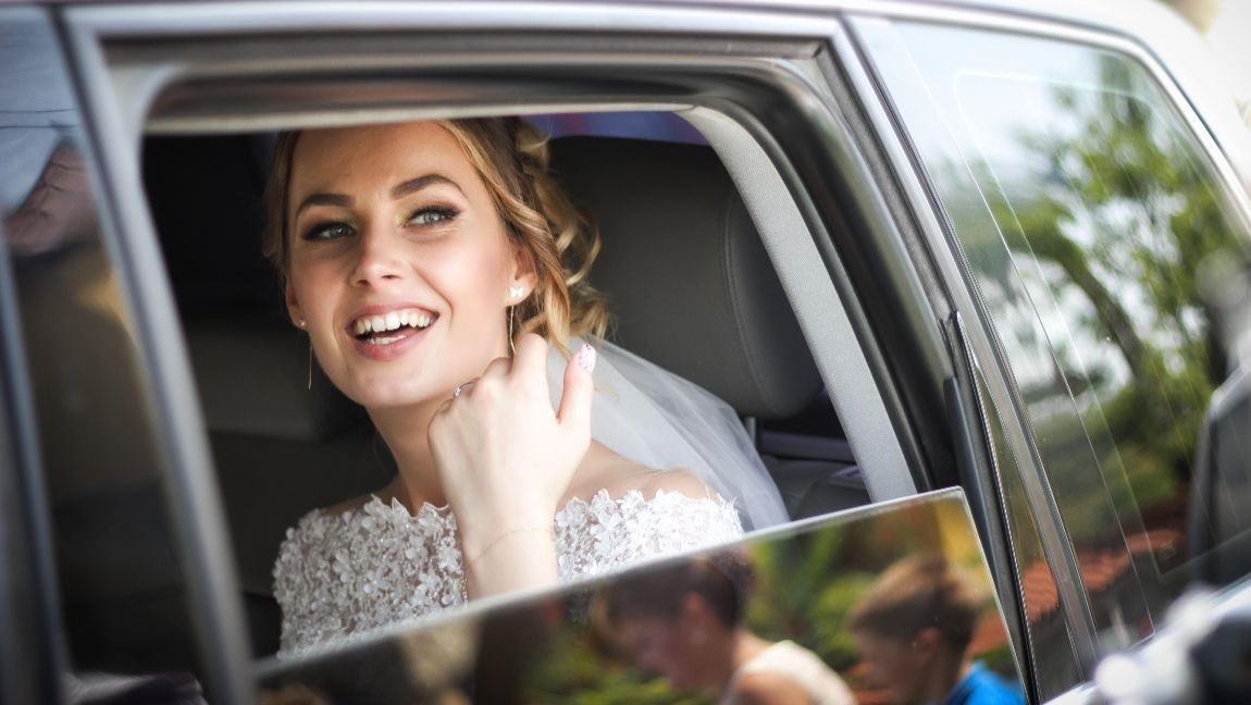 A white woman wearing a wedding dress is laughing from inside a car with the window open.