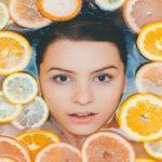 A face of a woman surrounded by slices of lemons in a body of water.