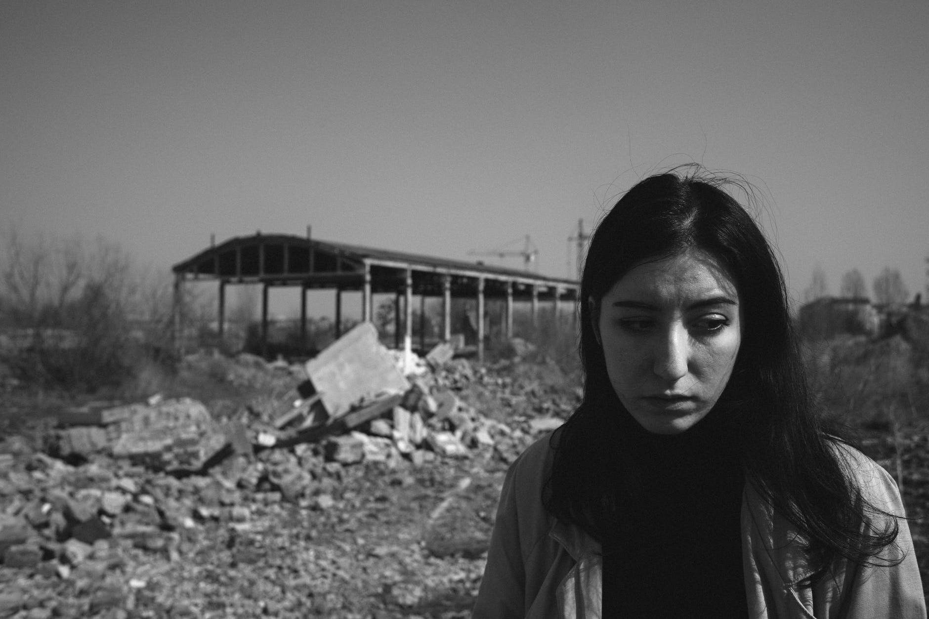 [Black & white image showing a girl standing, desperately, and behind her a destroyed building.] war