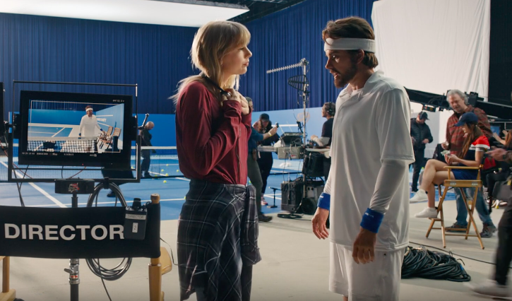 [Image description: Taylor Swift in movie set talking to another Taylor dressed as a guy in a sport outfit. Next to them is a director chair.]