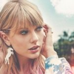 [Image description: Taylor Swift putting her hair behind her ears and looking to the side. She has pink highlights in her hair, a unicorn earring and a blue and white dress.] Via Google