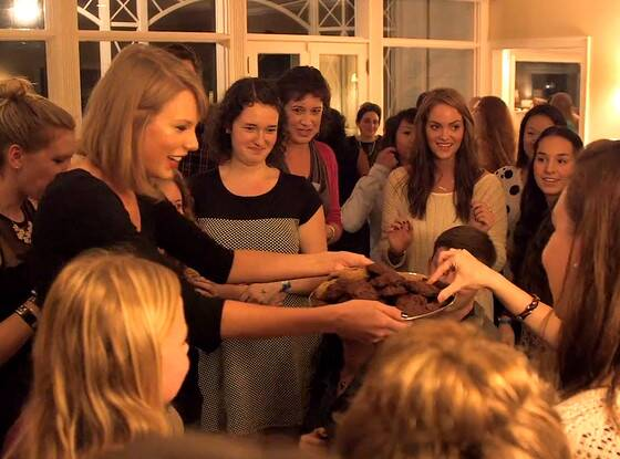 [Image description: Taylor Swift in a black dress holding a plate of chocolate cookies to a group of girls.]