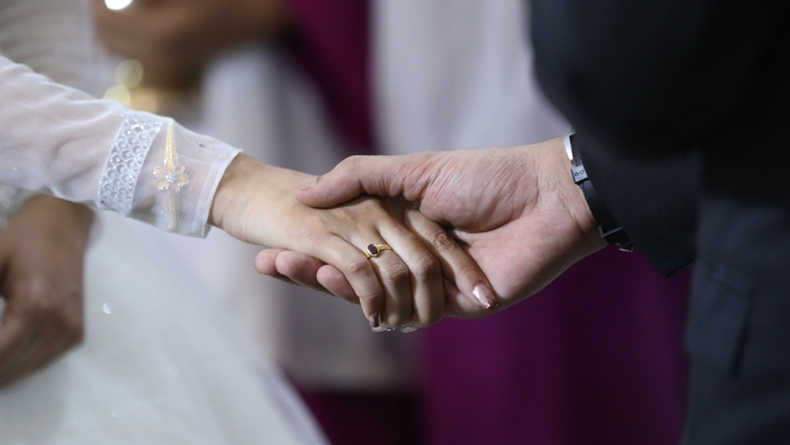 (Photograph of a man and woman holding hands. Woman is wearing a wedding ring on her hand, and is dressed in white) via Pexels.