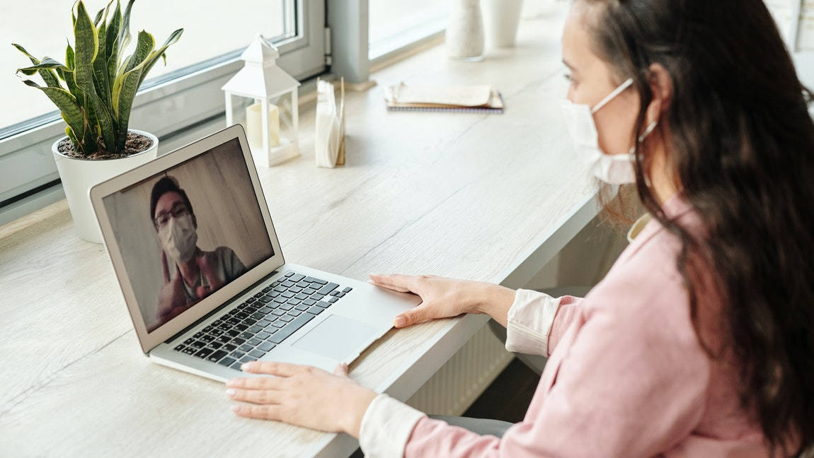 [Image description: a dark haired woman with a face mask sits on a white desk and has a video call with a man who is also wearing a mask] via Edward Jenner on Pexels.