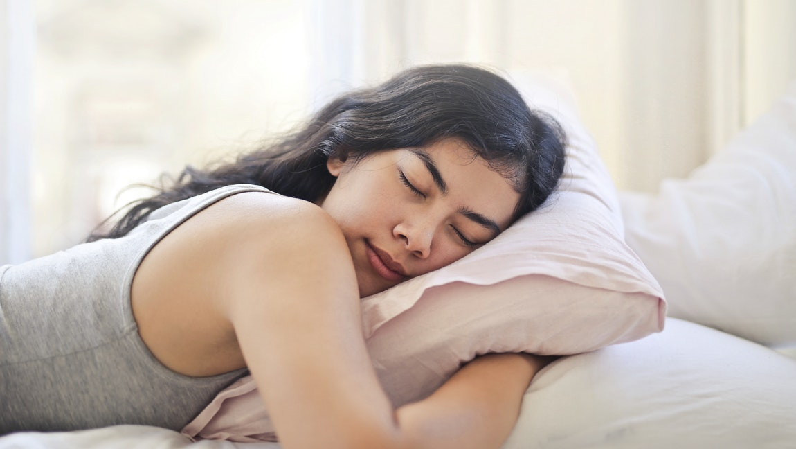 A woman is asleep, having dreams, and hugging a pillow.