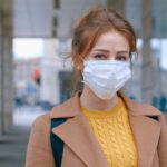 Attribution: [Image description: Brown-haired woman wearing a face mask on the street.] Via Anna Shvets on Pexels