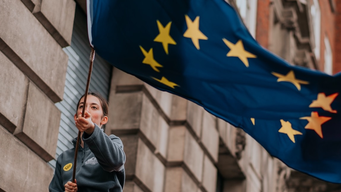 [Image description: A woman holding an EU flag.] via Brunel Johnson on Unsplash