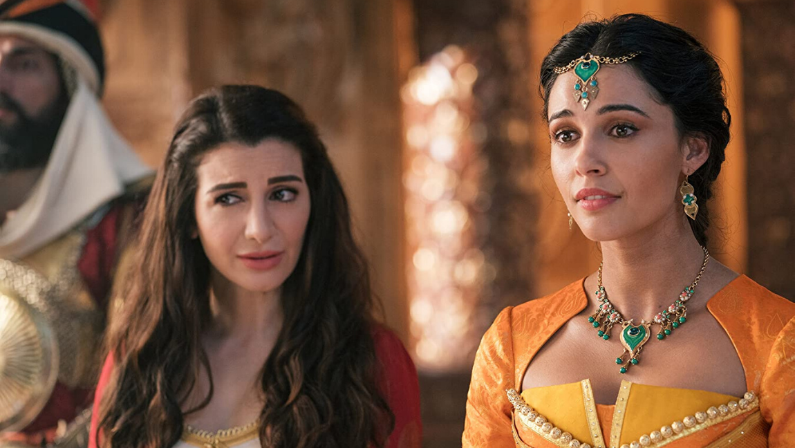 Attribution: [Image description: Still from (Aladdin): A woman in orange wearing jewellery with green accents, and a lady wearing red look quizzically at someone out of frame.] via imdb.com