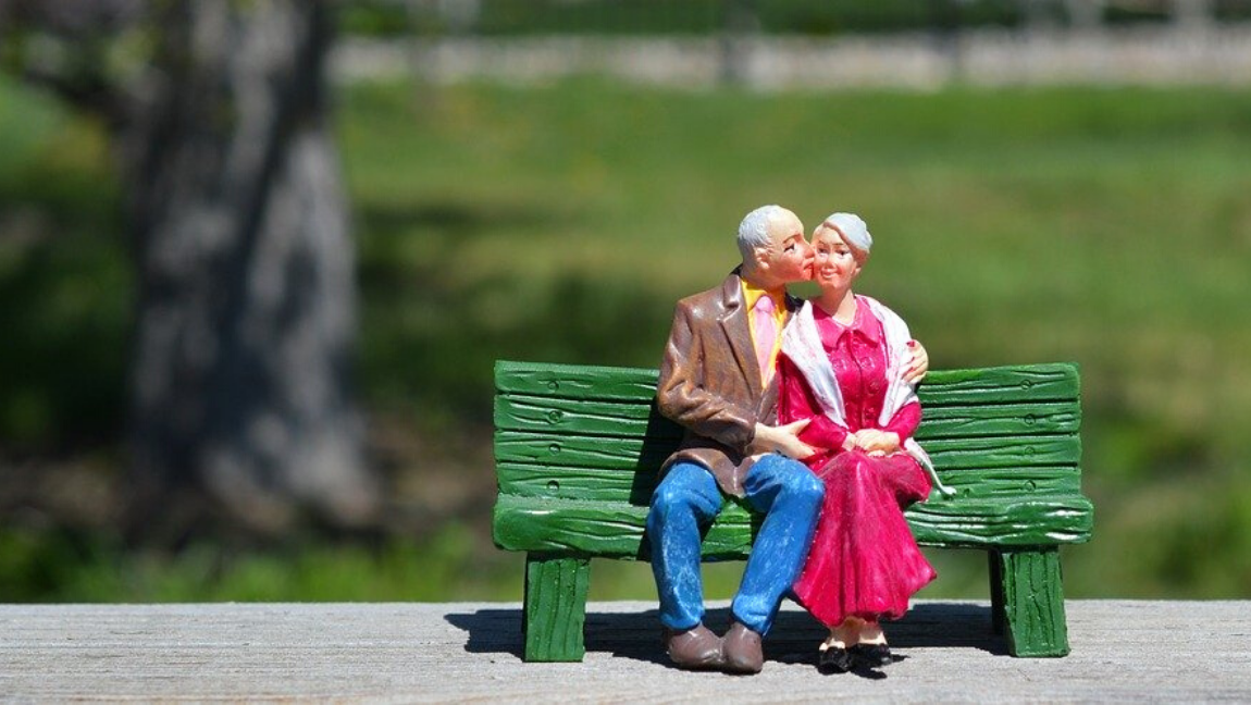 [Image description: A figurine of an elderly couple sitting on a green bench.] via pixabay