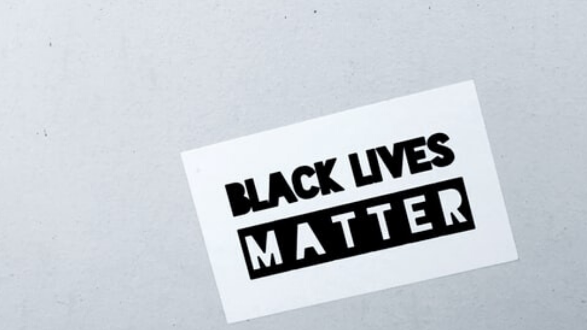 [Image Description: A black and white sign that reads 'Black Lives Matter'] Via Unsplash