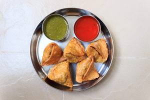 Image of five samosas with sides of green chutney and red sauce.