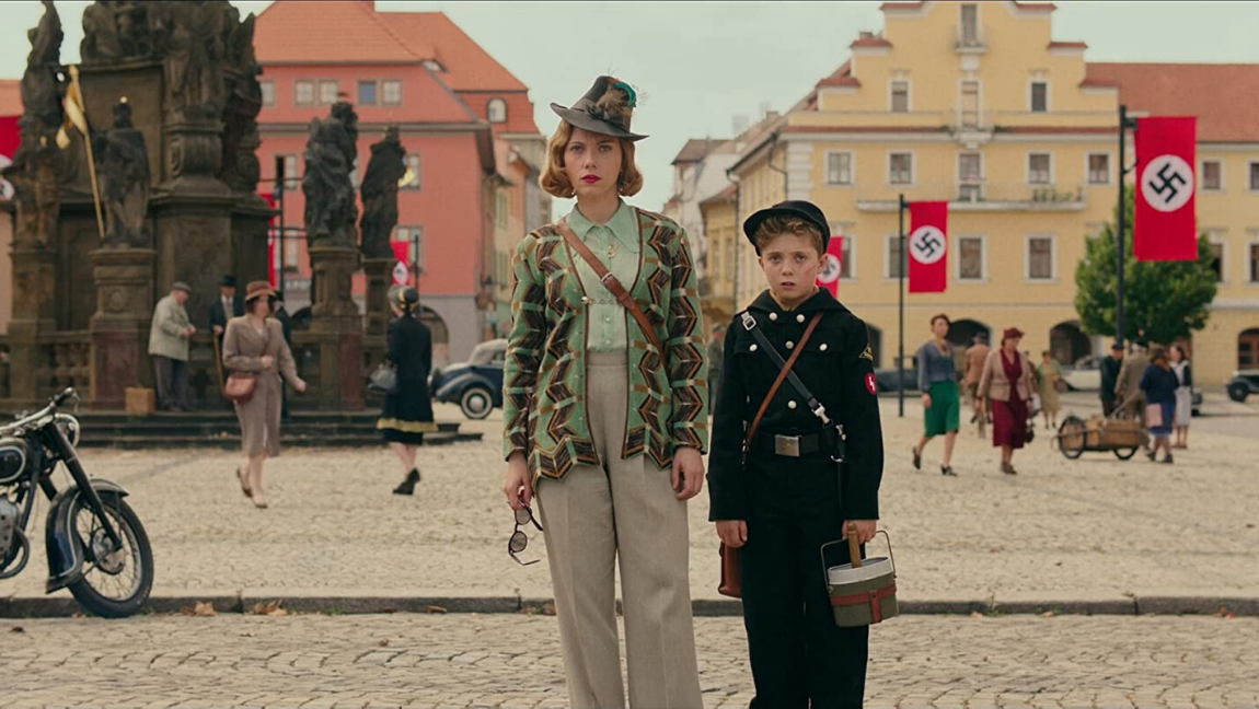 A still from Jojo Rabbit (2019). A woman wearing a feathered hat and holding sunglasses stands with a boy in a dark uniform holding a pail. There are Nazi flags visible in the background.