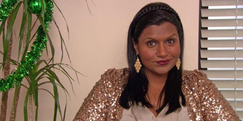 Kelly Kapoor wears statement earrings and a sequinned jacket.