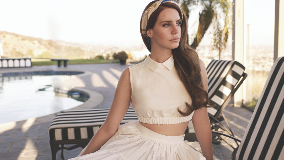 [Image Description: Singer Lana Del Rey is sitting on a deck chair. She is wearing a white dress and facing away from the camera] Via Lana Del Rey