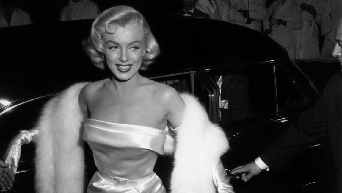 Black and white photograph of Marilyn Monroe wearing a strapless gown and long gloves, exiting a vehicle.