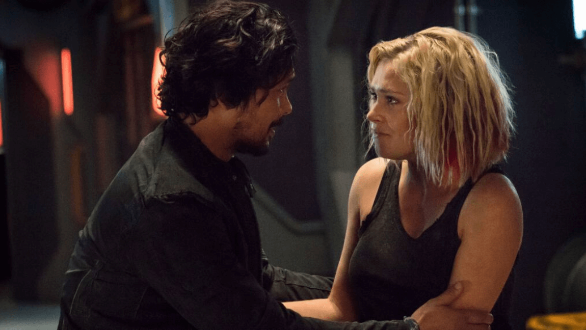 A dark-haired man and blonde woman - Bellarke - grip each other as they stare into each others' eyes.