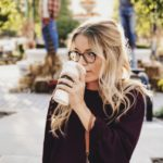 A blonde woman drinking coffee.