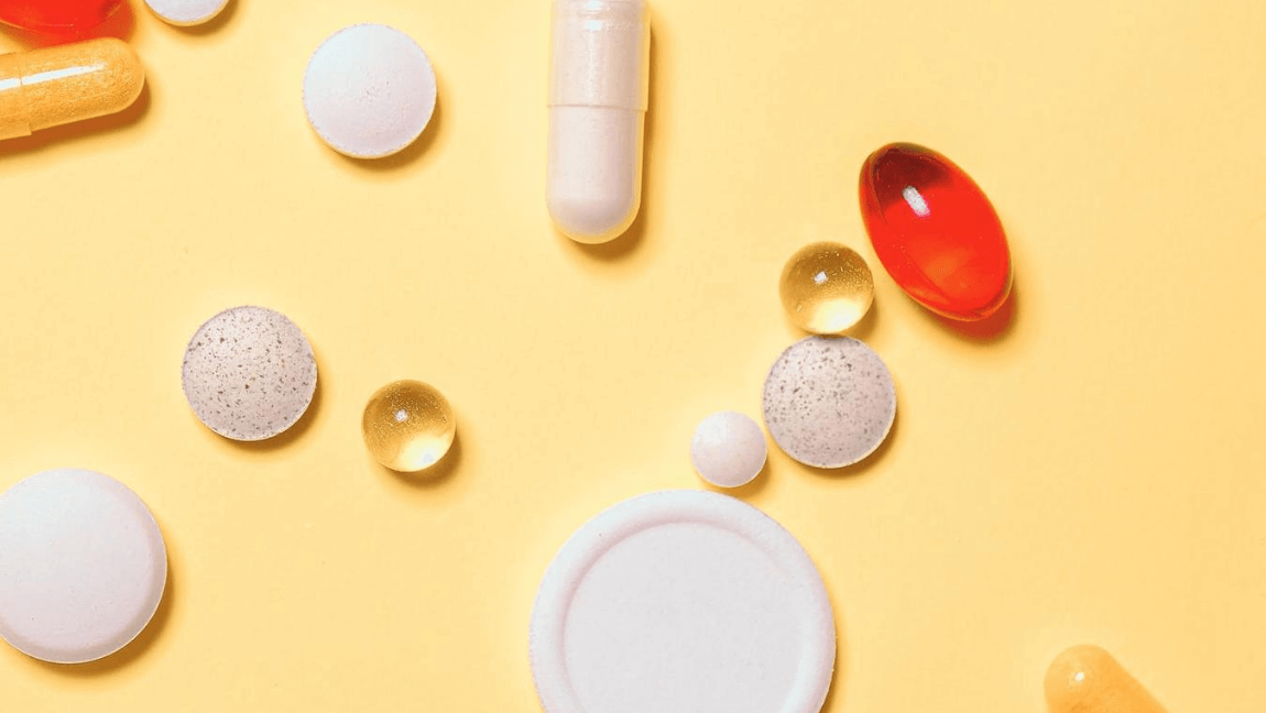 Different medicine pills set against a yellow background.