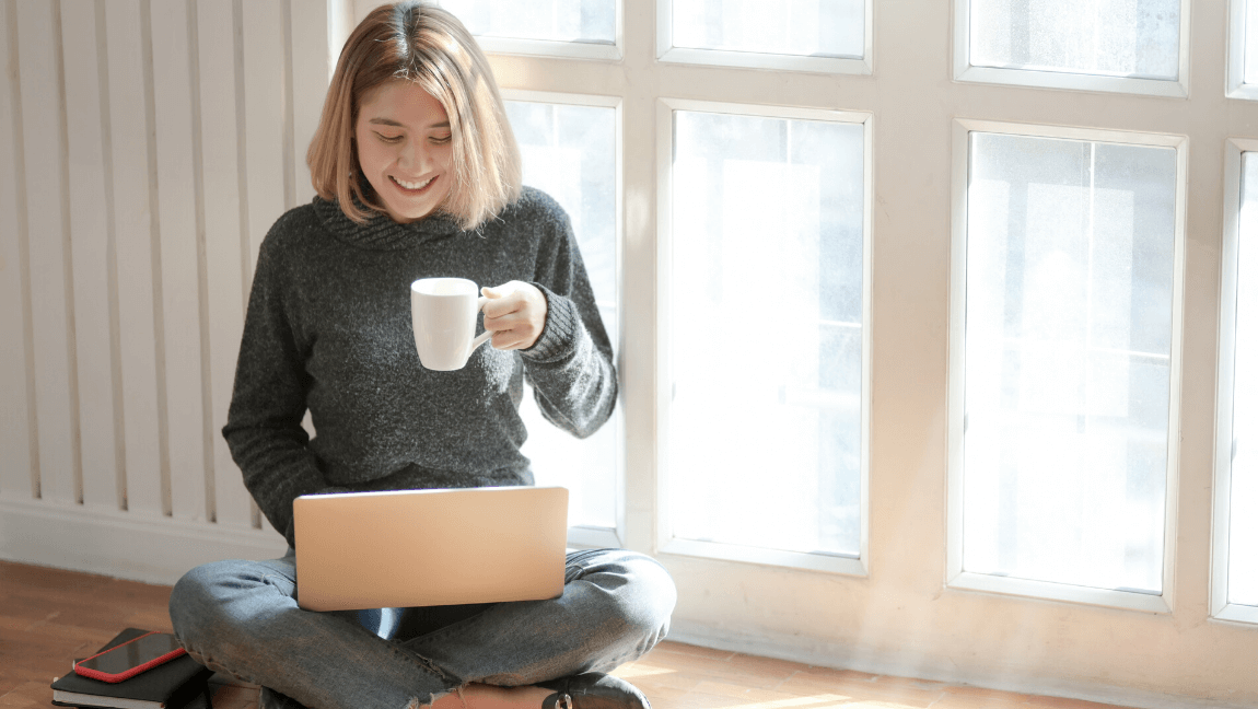 A young writer in a gray sweater sips coffee as she writes on her laptop.