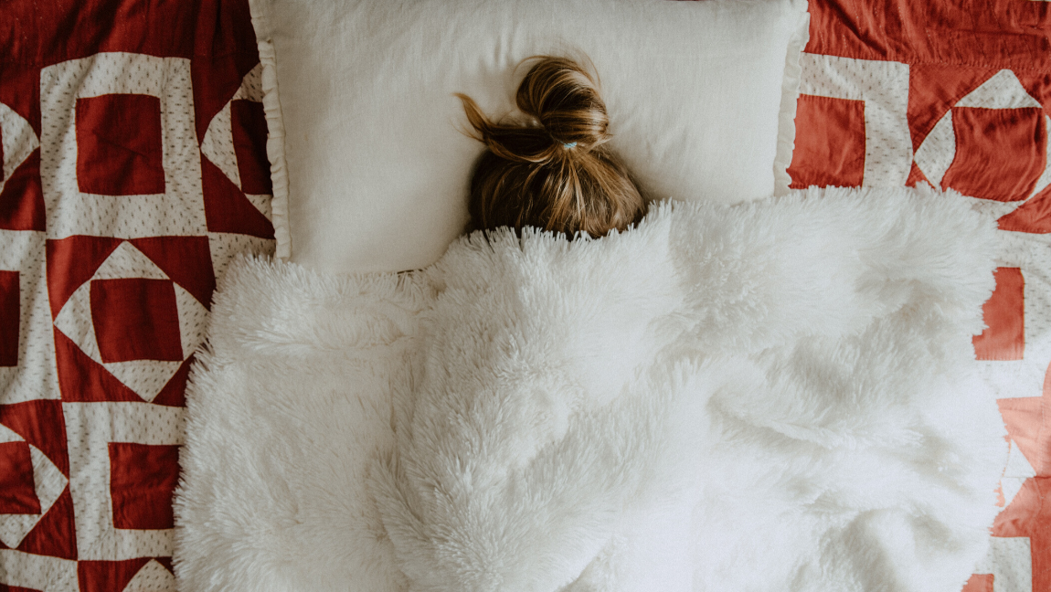 [Image description: A girl hides under a white blanket.] via Unsplash