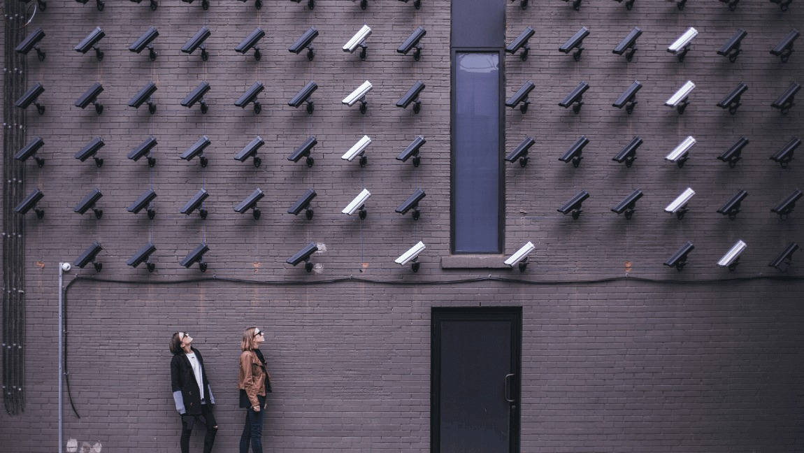 Two women look at security cameras positioned at them.