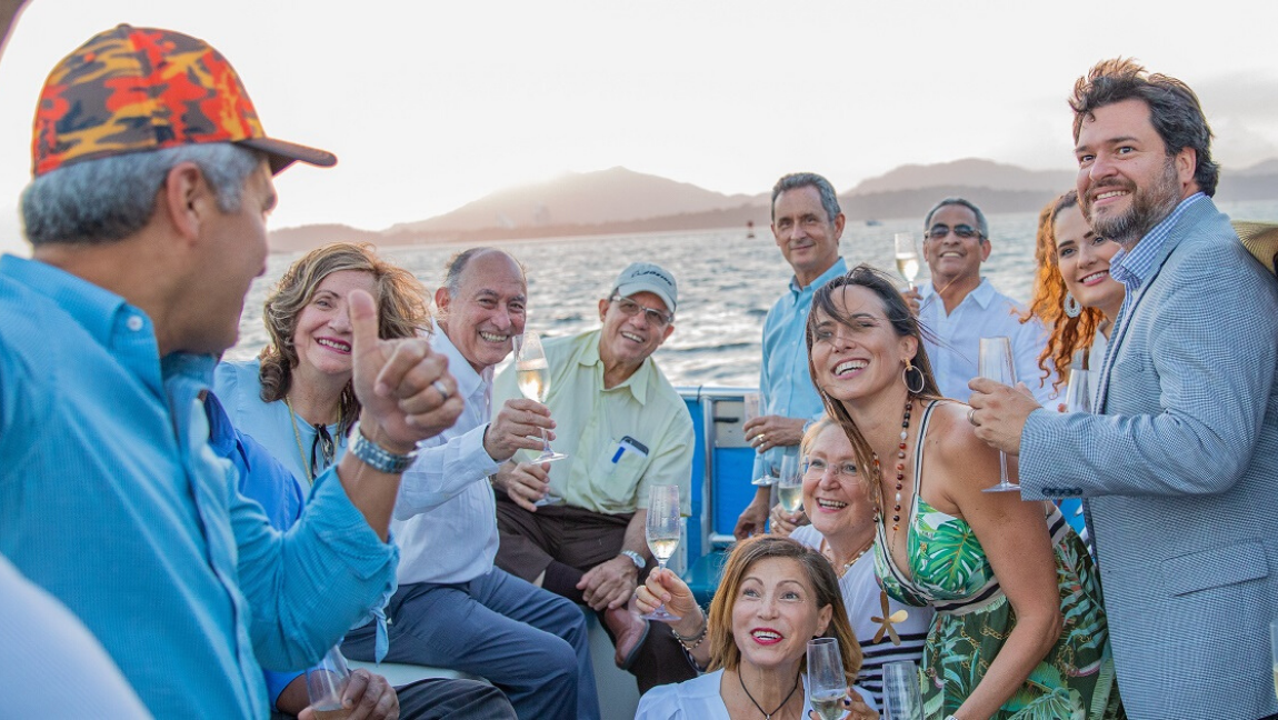 [A group of white people posing for a selfie at sunset with wine glasses raised high and smiles bright.] via Pexels