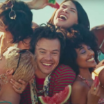 "[Image description: Harry Styles surrounded by models and fruit in the Watermelon Sugar video.] Via: Harry Styles, ""Watermelon Sugar"" on Billboard.com."