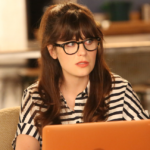 Jess from New Girl wearing glasses with a confused expression on her face